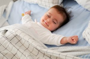 Baby smiling in bed with eyes closed and arms out.